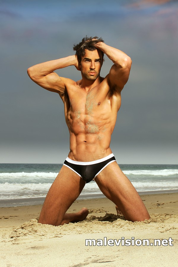 Sexy male model in fashion swimwear posing on the beach